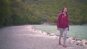 Uma menina atrativa em uma camisa de manta vermelha, levantando para a câmera A menina vai ao longo da costa do lago em um dia mo vídeos de arquivo