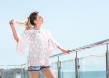 Uma menina atrativa está apreciando o verão e está olhando feliz Menina modelo nova encantador em um fundo brilhante do céu azul Fotos de Stock Royalty Free