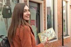 Uma menina atrativa está nas janelas, guardando um caderno Fotos de Stock