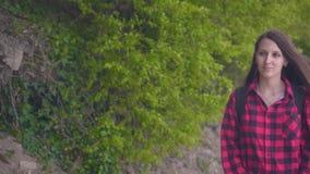 Uma menina atrativa nova em uma camisa quadriculado vermelha A menina vai na estrada ao longo dos arbustos verdes em um dia morno video estoque