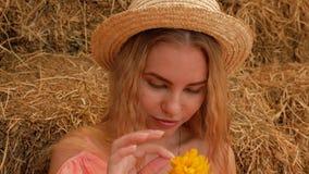 Uma menina atrativa nova em um chapéu de palha em um bom humor aspira uma flor amarela, a seguir rasga as pétalas dele e funde-as video estoque