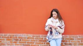 Uma menina atrativa nova está na parede de uma construção e pica um dedo em um telefone celular filme
