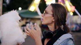 Uma menina atrativa que anda no parque do amusment, come o algodão doce branco Menina que veste a roupa ocasional, fones de ouvid video estoque