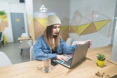 Uma menina autônomo bonita trabalha em um portátil em um café à moda do projeto Foto de Stock Royalty Free