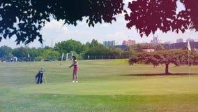 Uma menina bate uma bola, ao jogar o golfe em um campo Jogador de golfe em um campo de golfe filme