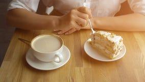 Uma menina bebe o café e come um bolo doce em um café A fêmea entrega o close up Imagens de Stock