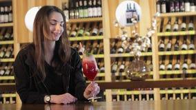 Uma menina bebe um cocktail vermelho na barra na barra, mulher que bebe o cocktail exótico vermelho vídeos de arquivo