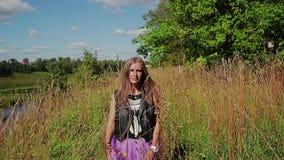 Uma menina bonita anda ao longo do banco alto do rio através da grama alta e de olhares ao lado e na câmera filme