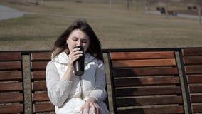 Uma menina bonita bebe o café de uma caneca thermo no parque em um banco e queima seus bordos vídeos de arquivo