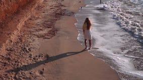 Uma menina bonita com cabelo longo, em um vestido amarelo-branco, anda com os pés descalços na areia amarela, praia, costa, mar N video estoque