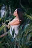 Uma menina bonita com corpo perfeito está levantando no parque do verão Forme a foto de uma jovem mulher no vestido 'sexy' no fun imagens de stock royalty free