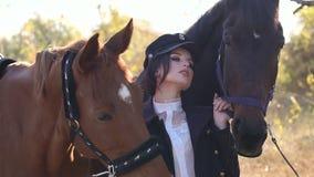 Uma menina bonita conduz dois cavalos bonitos atrás das rédeas no parque do outono filme
