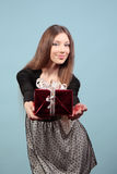 Uma menina bonita dá um presente Fotografia de Stock Royalty Free