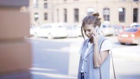 Uma menina bonita de sorriso dos jovens está tendo uma chamada fora fora Imagens de Stock