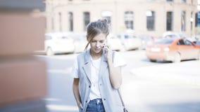 Uma menina bonita de sorriso dos jovens está tendo uma chamada fora fora Imagem de Stock