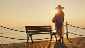 Uma menina bonita, delgada em um pareo tornando-se e um chapéu à moda largo-brimmed estão estando no cais, admirar imagem de stock