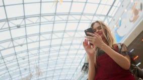 Uma menina bonita desce a escada rolante e fala no telefone na alameda vídeos de arquivo