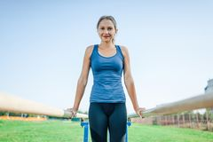 Uma menina bonita em uma camisa azul e nas caneleiras que fazem esportes nas barras desiguais que olham a câmera e o sorriso fotografia de stock