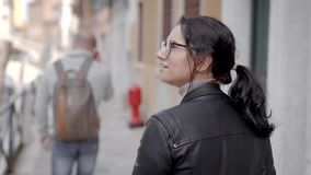 Uma menina bonita em um casaco de cabedal anda no italiano Veneza O turista da mulher está feliz sobre suas férias em Europa vídeos de arquivo