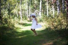 Uma menina bonita em um chapéu e em óculos de sol anda através da floresta em um dia ensolarado do verão Corre e dança Fotos de Stock
