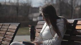 Uma menina bonita em um fato de esporte no parque no banco que lê um livro e que bebe o café de uma caneca térmica pontos a filme