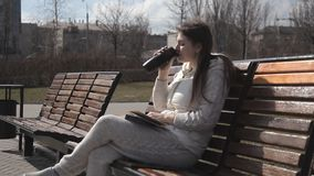 Uma menina bonita em um fato de esporte no parque no banco que lê um livro e que bebe o café de uma caneca térmica risos filme