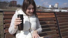 Uma menina bonita em um fato de esporte no parque no banco que lê um livro e que bebe o café de uma caneca térmica risos video estoque