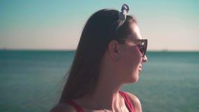 Uma menina bonita em um roupa de banho de uma peça só vermelho e suportes dos vidros no litoral nos raios do sol do por do sol vídeos de arquivo