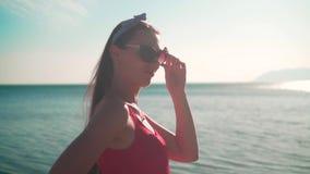 Uma menina bonita em um roupa de banho de uma peça só vermelho e suportes dos vidros no litoral nos raios do sol do por do sol filme