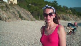 Uma menina bonita em um roupa de banho de uma peça só vermelho e em vidros está estando no litoral e no sorriso video estoque