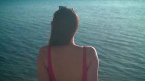 Uma menina bonita em um roupa de banho de uma peça só vermelho senta-se no litoral no sol do por do sol A menina senta-se para tr vídeos de arquivo