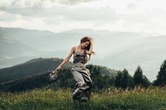Uma menina bonita em um vestido e um ramalhete das flores em sua mão Imagem de Stock