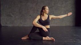 Uma menina bonita, esperta, atlética faz exercícios da ioga em um gym no estilo do sótão, com luz natural das grandes janelas ela filme