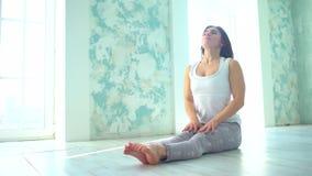 Uma menina bonita, esperta, atlética faz exercícios da ioga em um gym no estilo do sótão, com luz natural das grandes janelas ela video estoque