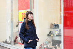 Uma menina bonita está estando pela janela de uma loja da forma Foto de Stock