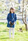 Uma menina bonita está guardando uma câmera em suas mãos imagens de stock