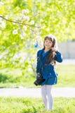 Uma menina bonita está guardando uma câmera em suas mãos foto de stock