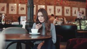 Uma menina bonita está sentando-se em uma casa do café e está texting uma mensagem em seu telefone celular video estoque