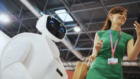 Uma menina bonita faz o selfie com um robô Namoradeira do robô com a mulher Tecnologias robóticos modernas O robô olha filme