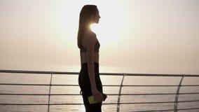 Uma menina bonita, graciosa anda no passeio na roupa dos esportes Os esportes engarrafam à disposição slim Sun brilha lento filme