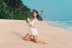 Uma menina bonita harmoniosa aprecia a praia, o sol e seu coco delicioso, ajoelhando-se na areia amarela morna europeu imagens de stock royalty free