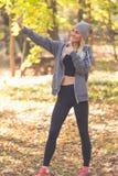 Uma menina bonita na floresta faz um selfie e mostra seu thum fotos de stock royalty free