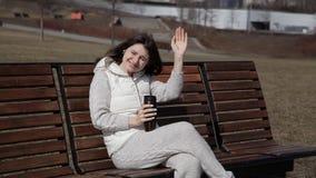 Uma menina bonita no parque em um café bebendo do banco de uma caneca térmica e de chamar alguém filme