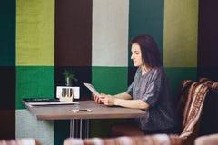 Uma menina bonita nos vidros lê um menu em um café fotografia de stock