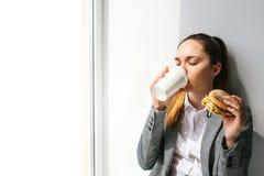 Uma menina bonita nova bebe o café ao lado de uma janela e come um hamburguer em uma ruptura entre o trabalho Fast food fotografia de stock royalty free