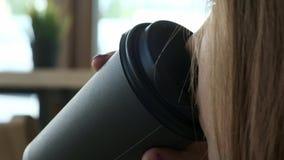 Uma menina bonita nova em um café à moda bebe o café na manhã antes do trabalho Senta-se oposto à janela Bebe filme