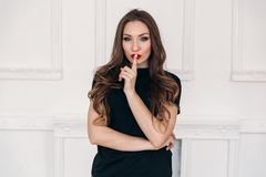 Uma menina bonita nova em um fundo branco que veste um t-shirt preto com bordos vermelhos, tem fólios escuros longos, chama para fotos de stock