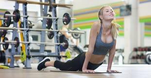 Uma menina bonita nova em um gym, inclinando-se em suas mãos, agita a imprensa, fazendo as etapas longas, dobrando seus joelhos C fotografia de stock royalty free