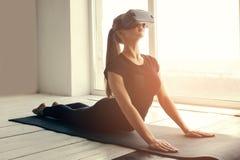 Uma menina bonita nova em vidros da realidade virtual faz a ioga e a ginástica aeróbica remotamente Conceito futuro da tecnologia Fotografia de Stock