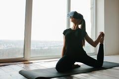Uma menina bonita nova em vidros da realidade virtual faz a ioga e a ginástica aeróbica remotamente Conceito futuro da tecnologia Fotos de Stock